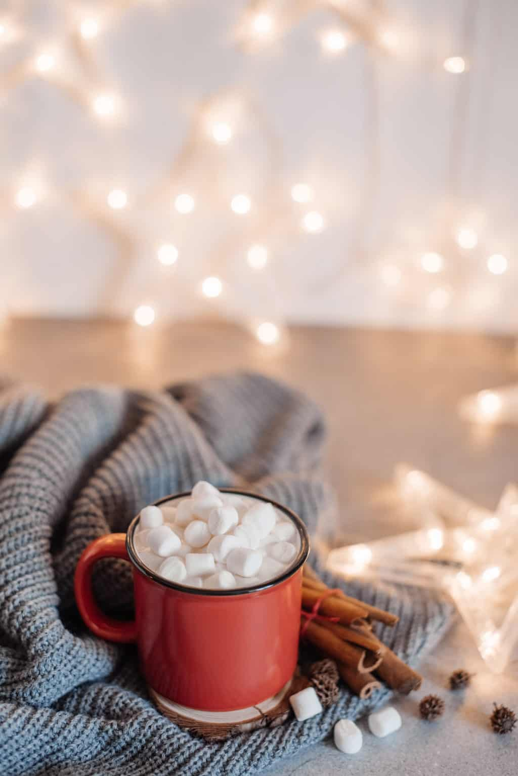 Red mugs with hot chocolate and marshmallows and gingerbread cookies. Christmas concept
